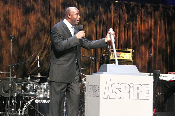 "As the crowd counted down, Earvin ""Magic"" Johnson pulled a large silver lever jutting from a box labeled ""ASPiRE."" With ..."