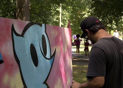 Tony Diaz worked alongside three other street artists to fill blank white boards with graffiti in the far center of ...