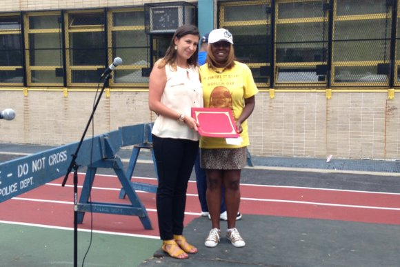 Vivian Montoya, associate manager of multicultural marketing at Colgate-Palmolive, pictured here with Tina McRae, Harlem Week Children's Festival organizer, presents ...
