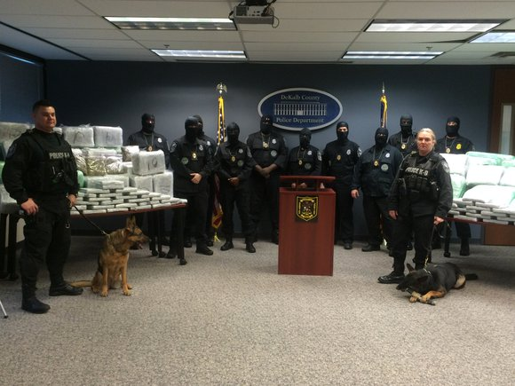 Masked undercover narcotics officers, drug sniffing dogs and detectives stood in front of hundreds of pounds of confiscated marijuana and ...