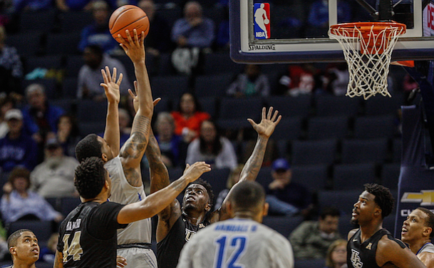 K.J. Lawson gets two of his 16 points while being closely guarded by Tank Efianayi (0)for UCF. (Photo: David Minkin)