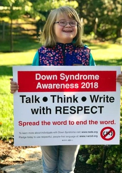 John F. Kennedy Middle School 7th grader Regan Reinertson poses with a sign for Down Syndrome Awareness Month.