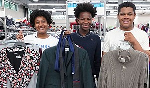 From right: Da'Shayla Foard, 17, from Irma Lerma Rangel Young Women's Leadership School; Demarre Johnson, 16, from the School of Business and Management at Yvonne A. Ewell Townview; and Adam Gaddis, 16, from Emmett J. Conrad, who will be a senior during the upcoming school year, shop at VolunteerNow for business clothes they will need for their upcoming internships.