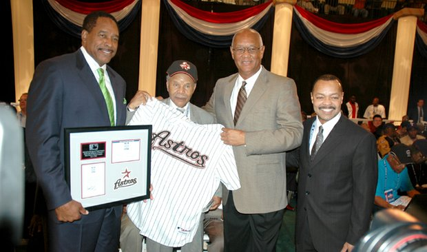 Bill Blair, second from left, is presented with his official Houston Astros jersey after the former Negro League baseball player was ceremoniously drafted by the Astros. Blair stands with (l. to r.) Dave Winfield, founder of the Negro League draft, Enos Cabell, special assistant to the general manager for the Astros and Jimmie Lee Solomon, executive vice president of Major League Baseball.