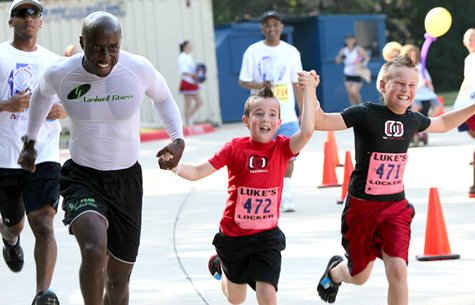 Children and adult runners race to the finish line during the 2012 Free to Breathe Dallas/Fort Worth Run/Walk.