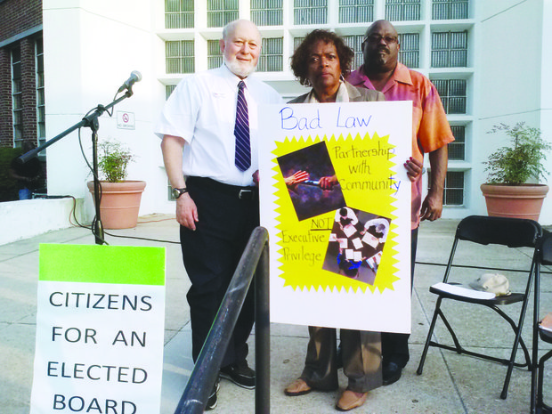 Citizens for an Elected Board organizers David Cahn (left) and Janis Hagey stand with talk show host Thomas K. Byrd at a press conference in front of Prince George's County Public School administrative offices in Upper Marlboro. The group is collecting petitions to force a referendum vote on changes to the management of the school system.