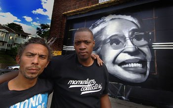Cedric Douglas (L) and Percy Fortini-Wright pause for the camera after finishing their mural of civil rights icon Rosa Parks earlier this month. The two were part of Mural Fest, which brought together over 80 Boston artists to transform a deserted parcel of land just outside of Dudley Square in Roxbury into the largest public art event and collection of street art in the history of the city.