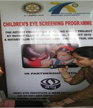 A volunteer teaches children and their parents about eye health in Mumbai, India.