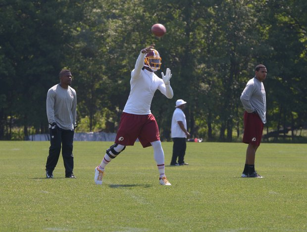 Washington Redskins quarterback Robert Griffin III throws a pass during NFL football training activity at Redskins Park in Ashburn, Va., Thursday, May 30.
