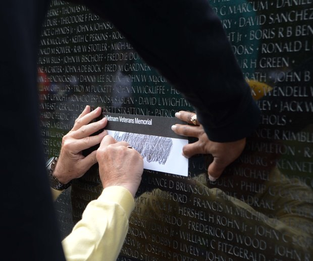 A volunteer traces a name at the Vietnam Memorial on Monday, May 27, 2013.