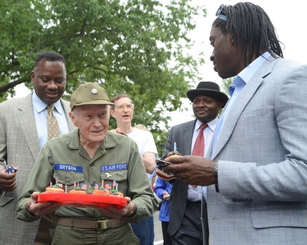 WWII Veteran Lt. Colonel Sam Bryson, 89 receives birthday wishes from Robert Griffin Jr. and Robert Griffin III after the Memorial Day parade on Monday, May 27, 2013.