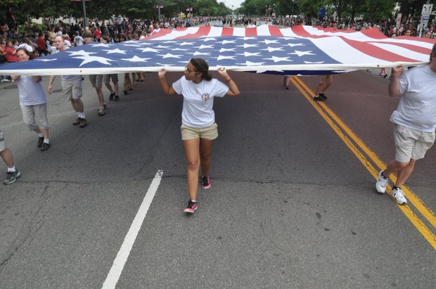 Flag bearers participate in the 9th Annual National Memorial Day Parade on Monday, May 27, 2013 in Northwest.