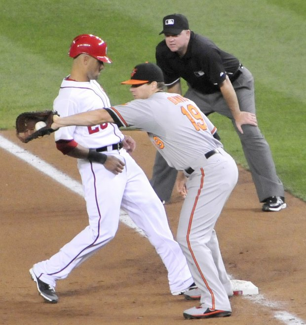 Baltimore Orioles first baseman Chris Davis is late collecting the baseball as Washington Nationals shortstop Ian Desmond reaches home safely under the watchful eyes of first base umpire Ron Kulpa on May 28 at Nationals Park in Southeast. The Nationals defeated the Baltimore Orioles 9-3.