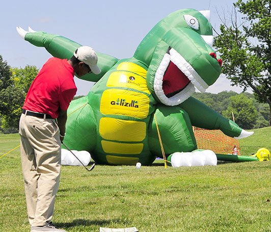 A golfer tries his luck at hitting a  golf ball into the mouth of a blow-up Godzilla at the Langston Golf Heritage Celebration in Northeast on Saturday, June 8.