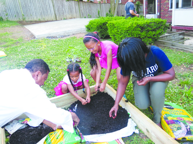 From left: Ron Harris of Howard University helps Dakota and Taleyah Evans along with Howard University medical student, Stephanie Purnell, in creating their garden for the My Garden project sponsored by the Howard University College of Medicine in Northwest on June 8.