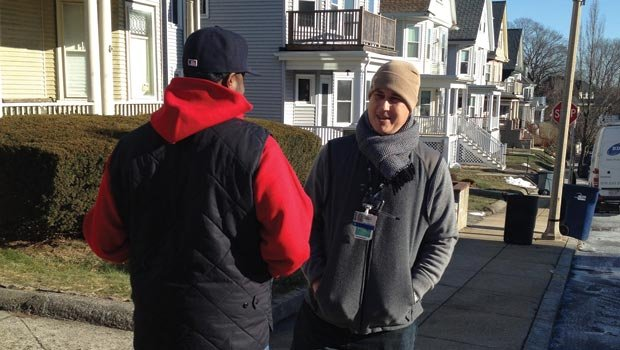 David Crump, Violence Recovery Specialist for Brigham and Women's Hospital, talks with a client in a Boston neighborhood.