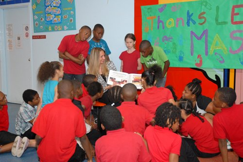 """Jennifer Beyers, manager, Community Relations and Volunteerism, Legg Mason & Co., LLC reads the fairytale book authored and illustrated by fourth and fifth grade students at Dr. Rayner Brown Academy on Monday, June 10, 2013. The students participated in HFI's unique educational program """"Bringing Enchanted Tales to Life."""" Each student  received their own copy of the hardbound book."""