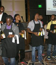 Torrey Smith (rear) was joined by several of his teammates who served Four Season cuisine wearing chef coats and aprons to those attenting the event.