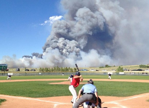Photo of a baseball game with smoke in background from fire in Colorado. Two ferocious wildfires are roaring across the region, scorching thousands of acres and devouring dozens of homes.