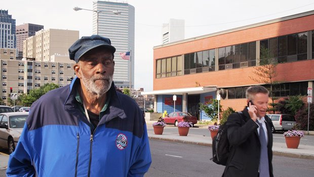 Mel King stands across the street from the former site of his childhood home that became the headquarters of the Boston Herald. A Newton-based developer wants to develop luxury condos on the site.