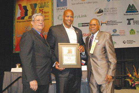 Mel Jones (center) of Skanska USA, accepts a construction industry award to the company's Portland office from the Oregon Association of Minority Entrepreneurs, represented by Jorge Guerra (left) and Sam Brooks (right).