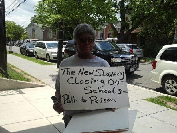 ANC Commissioner Kay Armstead displays a sign explaining the sentiments of residents in Ward 8 who oppose the closings of neighborhood schools. (Dorothy Rowley)