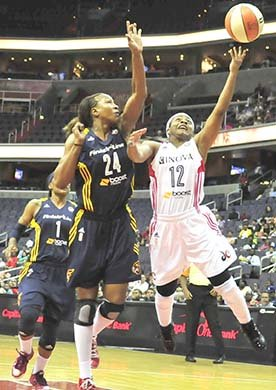 Mystics guard Ivory Latta gets around Indiana Fever forward Tamika Catchings in the first quarter of women's basketball action on ...