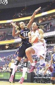 Mystics forward Monique Currie gets around Indiana Fever forward Tamika Catchings during women's basketball action on Sunday, June 16 at the Verizon Center in Northwest. The Mystics defeated Indiana 64-60.