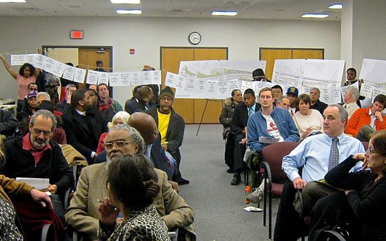 Attendees listen during a question-and-answer session at a March 6 meeting on the Melnea Cass Boulevard redesign project, while neighborhood activists display a 40-foot string of complaints about the project.