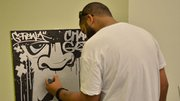 Towards the end of the evening artist Mike Lee, who graduated from graffiti art to graphic design, creates a piece of artwork before a small audience at the Juneteenth Takeover pop-up shop exhibition at the Museum of Fine Arts on June 19.