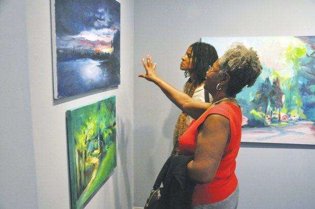 "Doris Watson (left) and Yvette Watson both admire a landscape painting by Norman Parish during the opening for the exhibit ""Norman Parish: The Artist"" at the Parish Gallery in Georgetown on June 21."