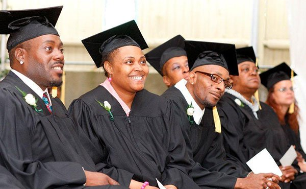 Graduates from Pine Street Inn's job training program listen to speakers during a recent graduation ceremony. The graduates, all homeless men and women, ranging in age from 20s to 60s, wore caps and gowns to celebrate the completion of the program, which featured training in food services, building maintenance and housekeeping.
