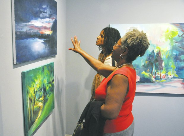 "Doris Watson (left) and Yvette Watson admire a landscape painting by Norman Parish during the opening of the exhibit ""Norman Parish: The Artist"" on June 21 at the Parish Gallery in Georgetown."