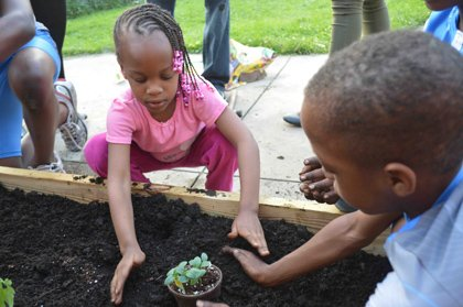 Nailah Muhammad, the youngest, and her older brother, Ameer Muhammad, gently cover up one of the vegetable plants. They planted tomatoes, basil, cucumbers, peas and beans. They also planted mint to keep bothersome insects away.