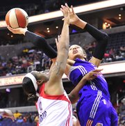 Phoenix Mercury's DeWanna Bonner shoots around Mystics player Kia Vaughn during the first quarter of WNBA action on Thursday, June 27, at the Verizon Center in Northwest. Bonner scored 22 points as the Mercury beat the Mystics 101-97.