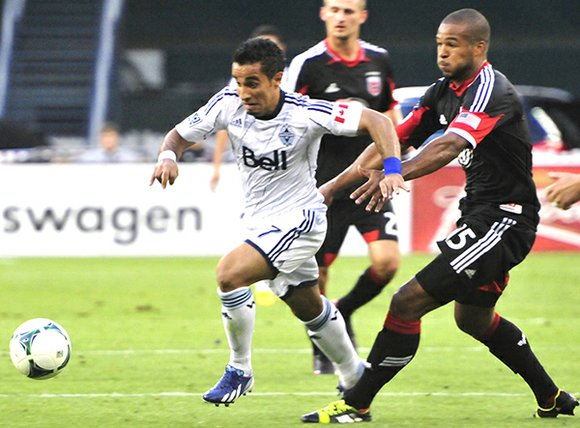 Vancouver Whitecaps forward Camilo Sanvezzo and D.C. United defender Ethan White fight for the ball in the second half of ...