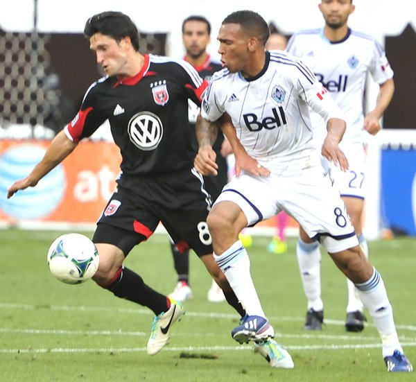 D.C. United midfielder John Thorrington, and Vancouver Whitecaps midfielder Matt Watson fight for possession of the soccer ball in the first half of Major League Soccer action on Saturday, June 29, at the Robert F. Kennedy Memorial Stadium in Southeast. Vancouver defeated the United 1-0 before 13,112 fans.
