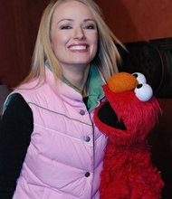 "Showbiz Tonight's Brooke Anderson poses with Elmo in the CNN suite at the Sundance Film Festival. Kevin Clash, the man who brings Elmo to life, is the subject of the Sundance documentary ""Being Elmo""."