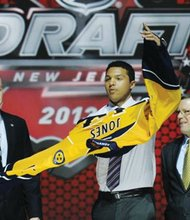 Seth Jones, a defenseman for the Portland Winterhawks and an 18-year-old from Aloha High School,  pulls on a Nashville Predators sweater after being chosen 4th overall in the first round of the NHL hockey draft, Sunday, June 30, 2013, in Newark, N.J.