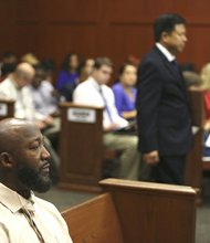 Trayvon Martin's father, Tracy Martin, sits in court as Volusia and Seminole County associate medical examiner Shiping Bao enters the courtroom to take the stand during George Zimmerman's trial in Seminole circuit court in Sanford, Fla. Friday, July 5, 2013. Zimmerman has been charged with second-degree murder for the 2012 shooting death of Trayvon Martin.