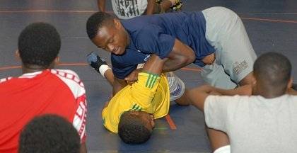 Beat the Streets camp volunteer Albert Woody demonstrates a wrestling move.