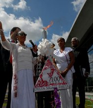 Dr. Thelma T. Daley, 16th National President of Delta Sigma Theta Sorority, Inc. lights torch; Bernadette Adams (Delta Sigma Theta member), Father Donald Sterling ,New All Saints Church
