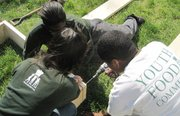 Three interns from the Food Project assemble a raised bed for a community member.