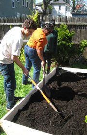 Brandy Brooks (center), the director of community programs at the Food Project, works with project youths to build a raised bed garden.