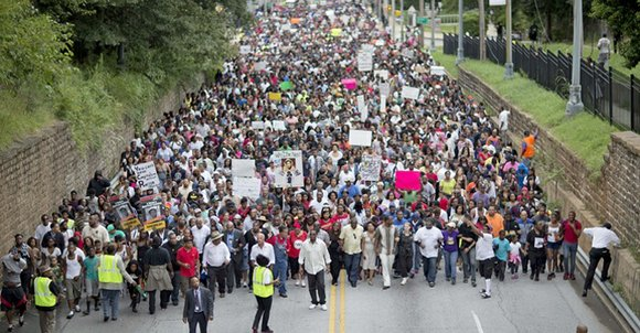 "Chanting ""Justice for Trayvon"" and ""No justice, no peace,"" a crowd that reached into the thousands marched from Atlanta's West ..."