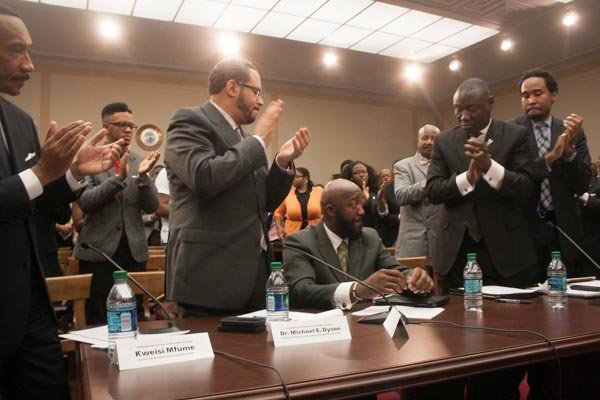 Tracy Martin (center) father of slain teenager, Trayvon Martin, receives a standing ovation for being an excellent parent during the standing room only inaugural Congressional Caucus Black Men and Boys hearing held Wed., July 24 at the Rayburn House Office Building in Southeast.  Martin was one of the panelists that included Kweise Mfume, former NAACP chief executive and Maryland Congressman, Michael Eric Dyson, sociology professor at Georgetown University in Northwest, Martin's attorney, Ben Crump, and David Johns, executive director of the White House Initiative on Educational Excellence for African Americans.