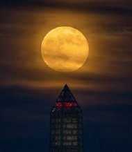 A supermoon rises behind the scaffolding-wrapped Washington Monument, Sunday, June 23, 2013.