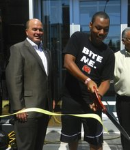 Smith (center), who waited in line for nearly 48 hours, cut the opening ceremony ribbon alongside property manager Michael Vercillo and the  president of Joe's Crab Shack, Jim Mazany.