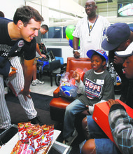 Mark Teixeira passing out gifts in the locker room to the HOPE Week youngsters