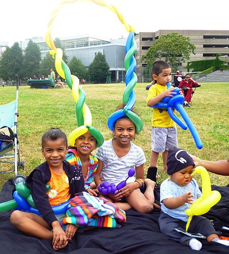 Yemilys Hernandez, 5, with her sisters Yaslaniz, 6, Yisarielie, 8, and Jose Ocasio, 3, all of the South End play with their free balloon creations at a ParkARTS Neighborhood Concert on July 22 at Carter Playground in the South End. The Mayor's Neighborhood Concerts feature a variety of music artists at parks throughout Boston until August 4. The event was sponsored by the Boston Parks and Recreation Department and in partnership with Bank of America and Northeastern University's City and Community Affairs. For information on more Boston Parks and Recreation Department events, please visit www.cityofboston.gov/parks.